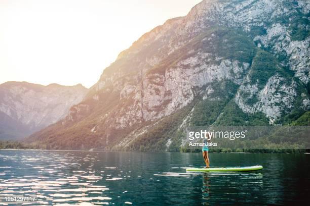 自然の中で孤独と美しさを楽しむパドルボード上の女性 - 30代の女性だけ ストックフォトと画像