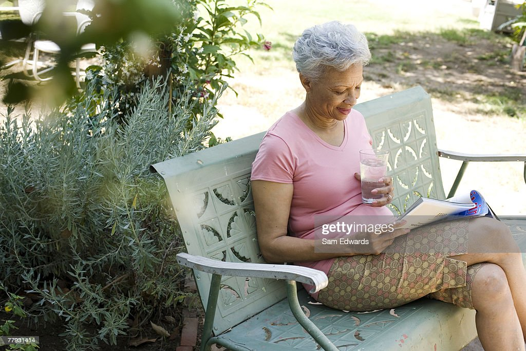 Woman on patio with magazine and glass of water : Stock Photo