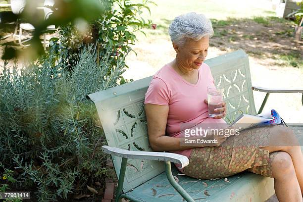 woman on patio with magazine and glass of water - glass magazine stock photos and pictures