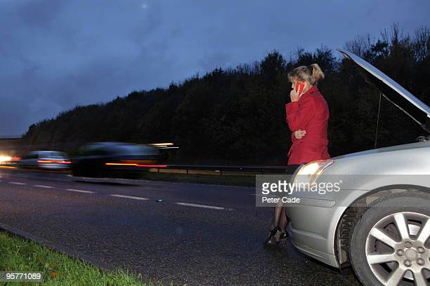 woman on phone, broken down at side of road