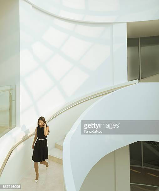 woman on phone descending staircase in modern building - wall building feature stock pictures, royalty-free photos & images