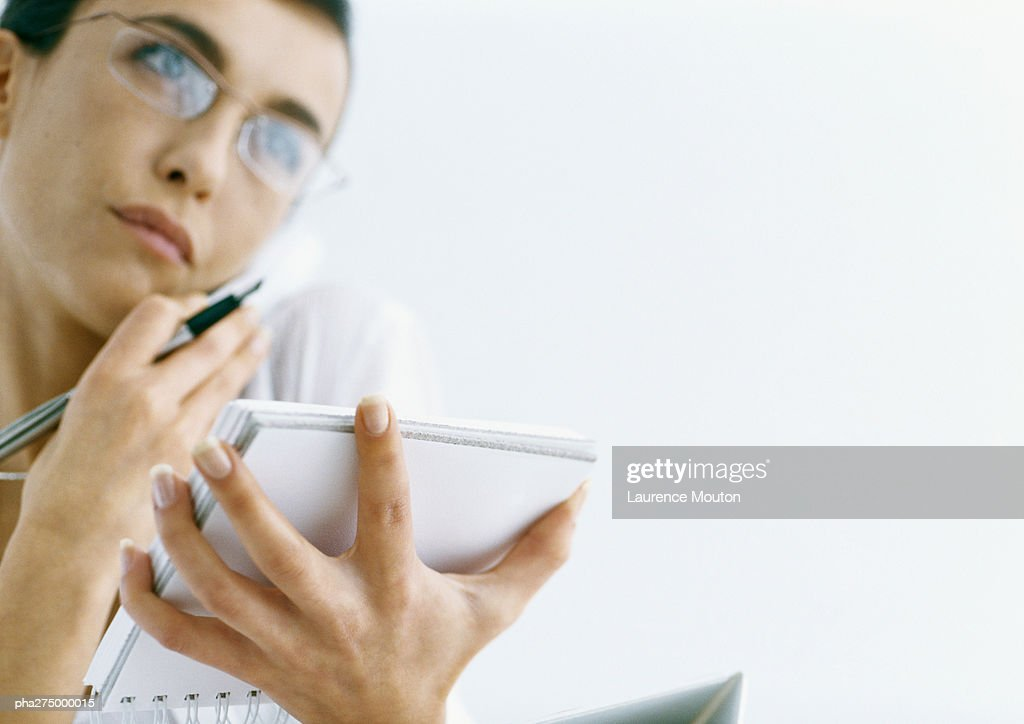 Woman on phone holding notepad and pen : Stockfoto
