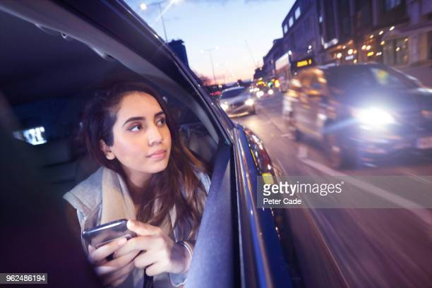 woman on phone in back of car, looking out of window - one young woman only stock pictures, royalty-free photos & images