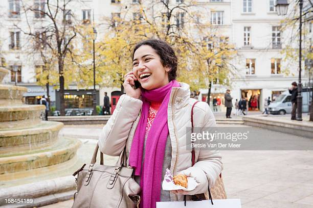 Woman on phone in shopping street, Paris.