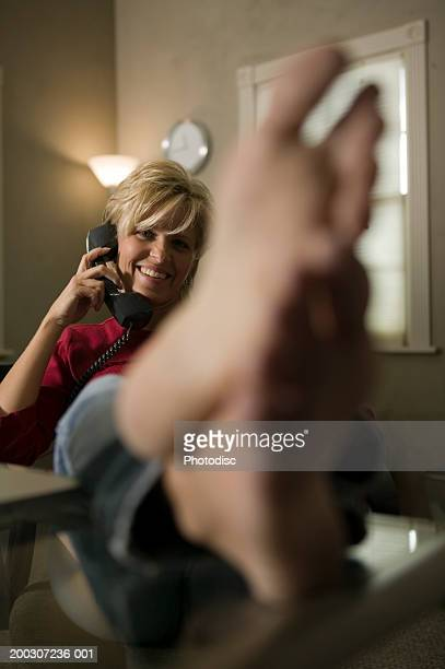 woman on phone, relaxing with feet on desk in office - donne bionde scalze foto e immagini stock