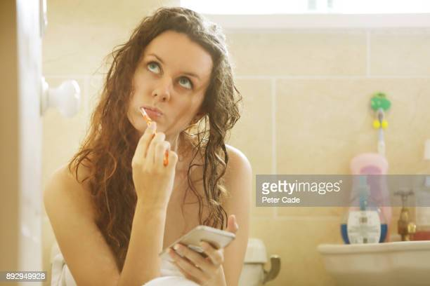 Woman on phone while cleaning teath in bathroom