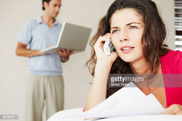 Woman on phone with bills and male