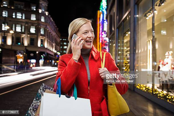 Woman on phone with shopping bags in city at night