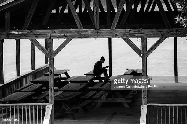 Woman on picnic table under wooden shelter