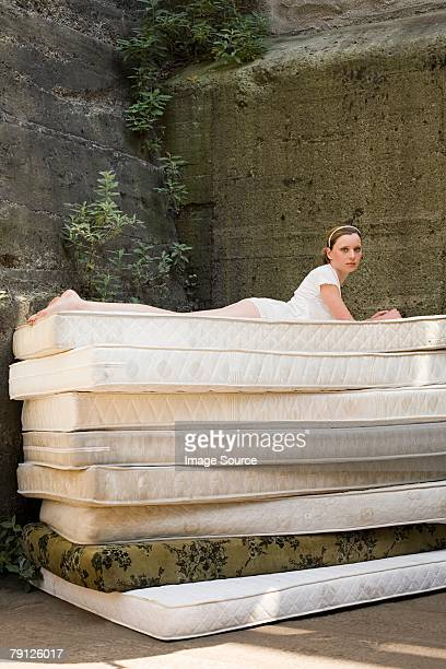 Woman on pile of mattresses