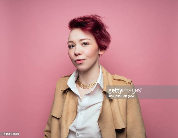 woman on pink background wearing leather jacket - redhead stock pictures, royalty-free photos & images