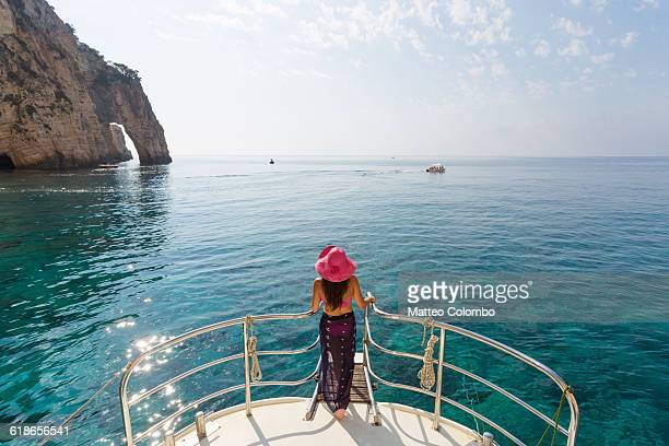 Woman on prow of sailboat in the blue sea, Greece