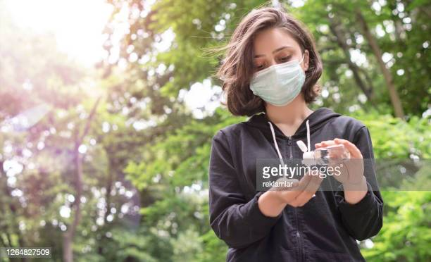 woman on public area with face mask. woman with face protective mask disinfectant her hand, coronavirus concept. - vivid filter. - cologne stock pictures, royalty-free photos & images