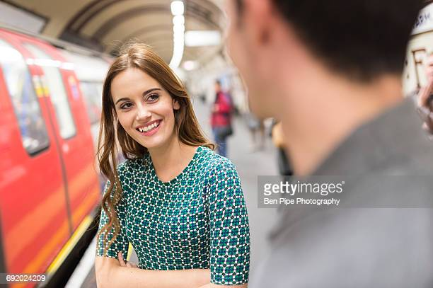 Woman on railway platform talking to friend