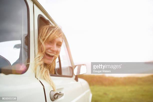 Woman on road trip looking out of car window and laughing.