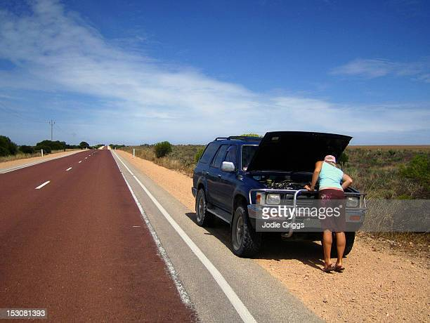 Woman on road with broken down car