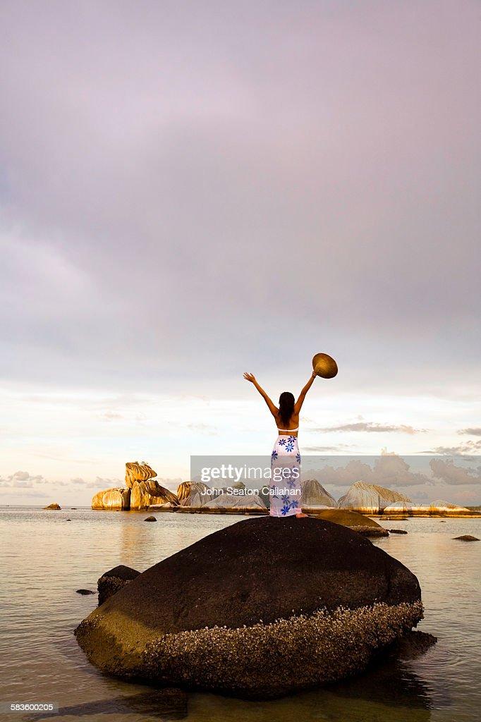 Woman on rock at sunset : Stock Photo