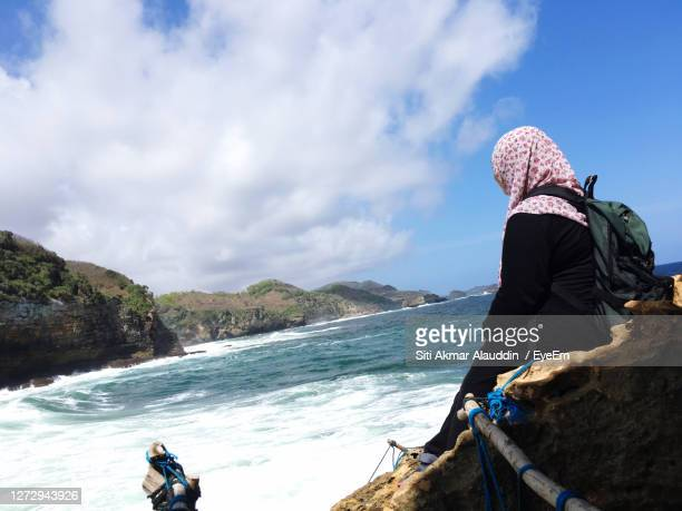 woman on rock by sea against sky - cari stock pictures, royalty-free photos & images