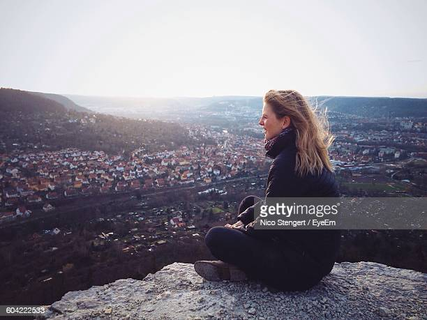 woman on rock looking at cityscape view against sky - テューリンゲン州 ストックフォトと画像