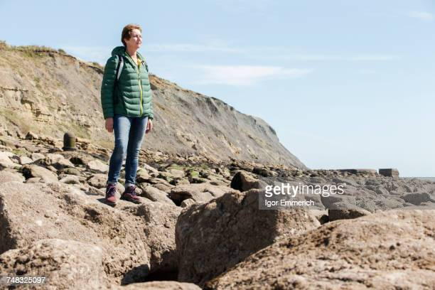 Woman on rock looking out to sea, Folkestone, UK