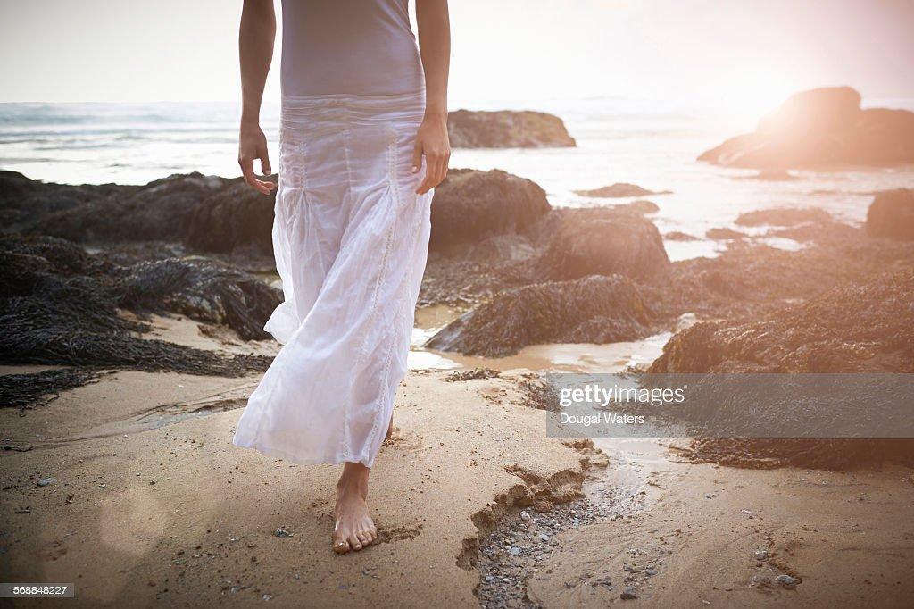 Woman on rocky beach at sunset. : Stock Photo