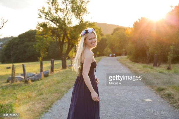 woman on rural road wearing strapless dress looking over shoulder at camera smiling - bridesmaid stock pictures, royalty-free photos & images