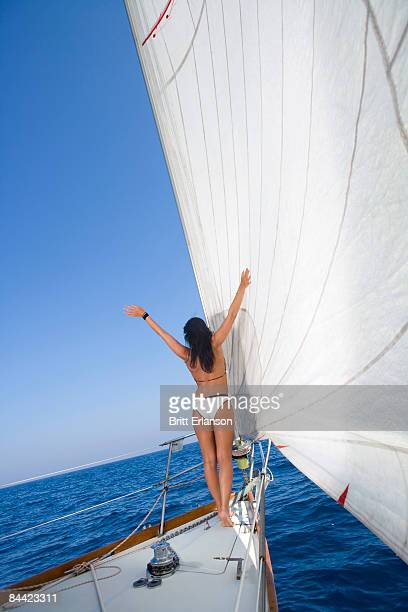 Woman on sailboat arms open