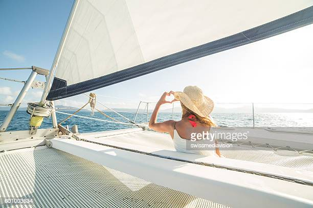woman on sailing boat makes heart shape finger frame - catamaran stock photos and pictures