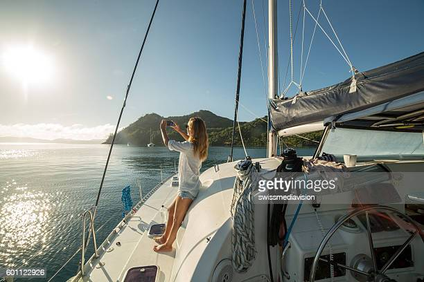woman on sailing boat photographing landscape with mobile phone - catamaran stock photos and pictures