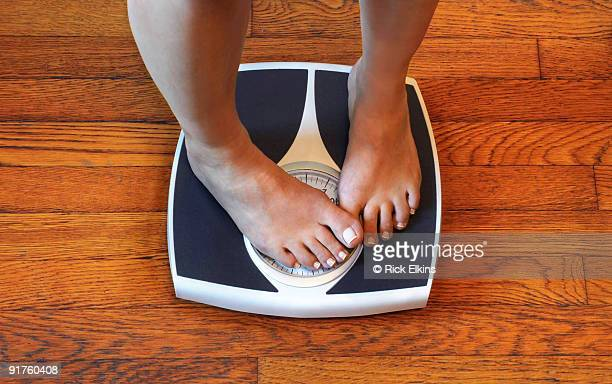 woman on scale unhappy with her weight - gordo fotografías e imágenes de stock