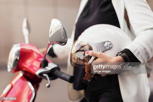 woman on scooter holding helmet - crash helmet stock pictures, royalty-free photos & images