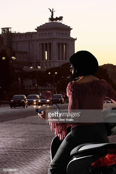 Woman on scooter in Rome using a mobile