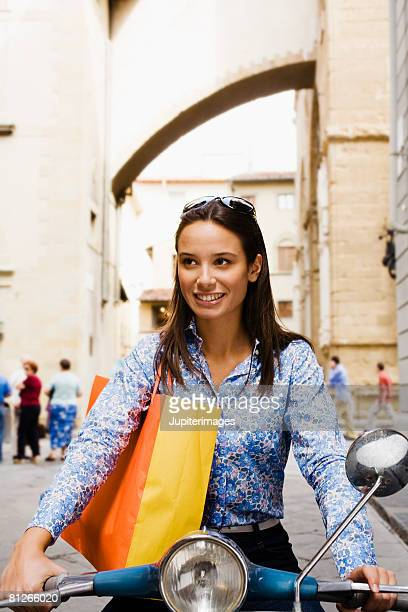 woman on scooter with shopping bag - moped stock photos and pictures