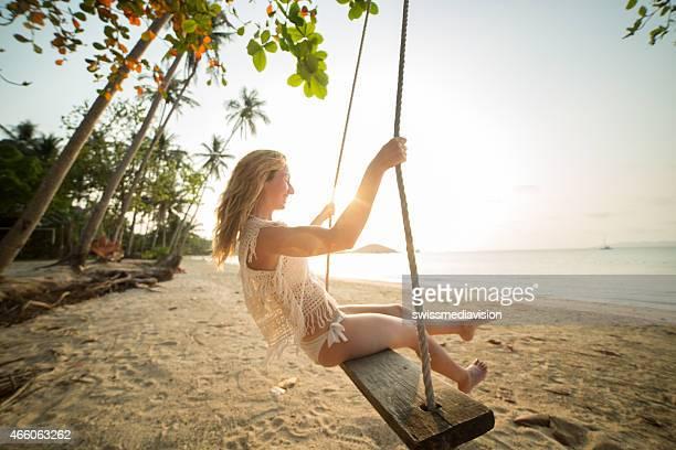 Woman on seasaw at tropical beach