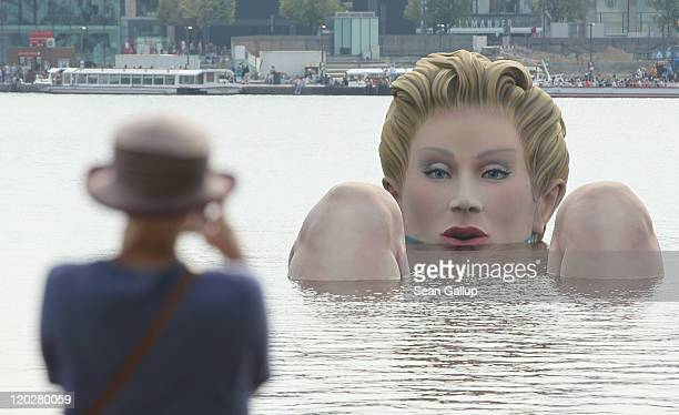 A woman on shore photographs Die Badende a giant sculpture showing a woman's head and knees as if she were resting in the Binnenalster lake on August...