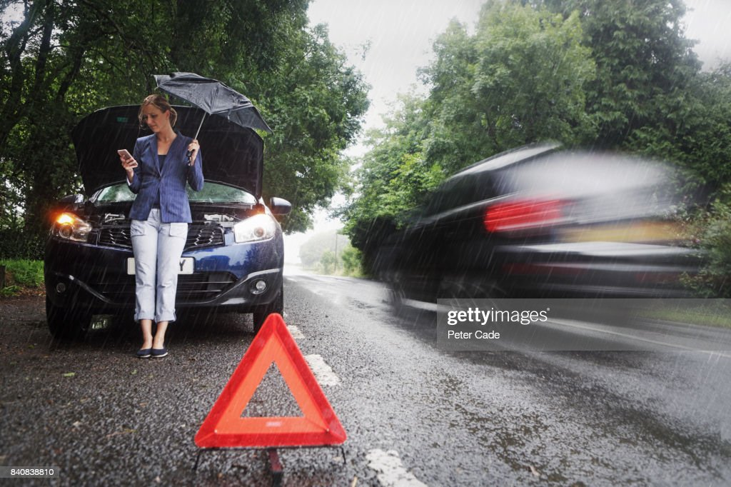 Woman on side of road with broken down car in the rain : Stock Photo