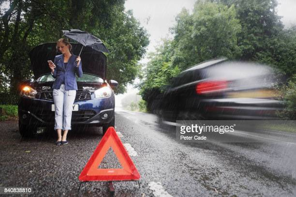 woman on side of road with broken down car in the rain - broken down car stock pictures, royalty-free photos & images