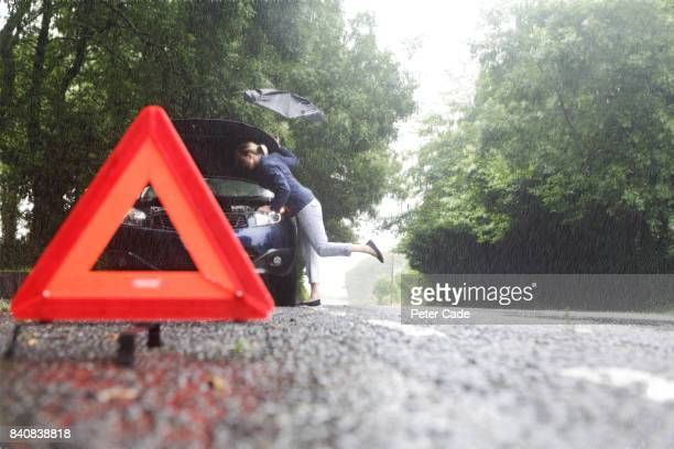 woman on side of road with broken down car in the rain - bad luck stock pictures, royalty-free photos & images