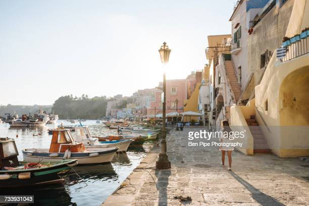 woman on sidewalk, island of procida, bay of naples, campania, italy - naples italy stock photos and pictures