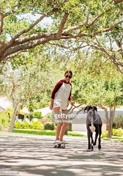 Woman on skate board with Great Dane