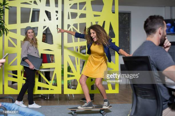 Woman on skateboard in office having fun