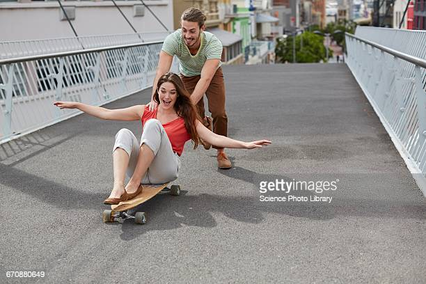 Woman on skateboard, man pushing