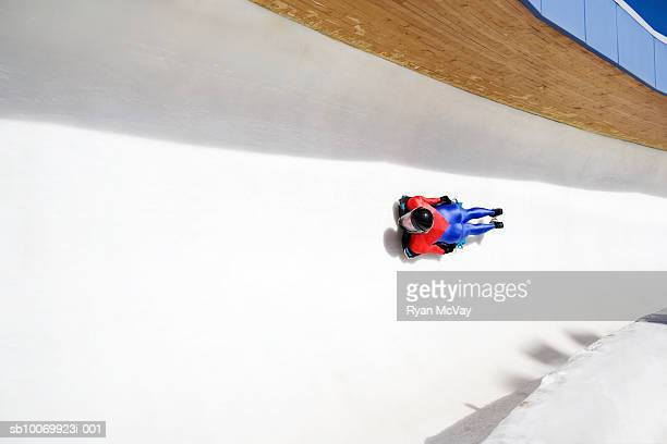 Woman on skeleton sled down ice track, high angle view