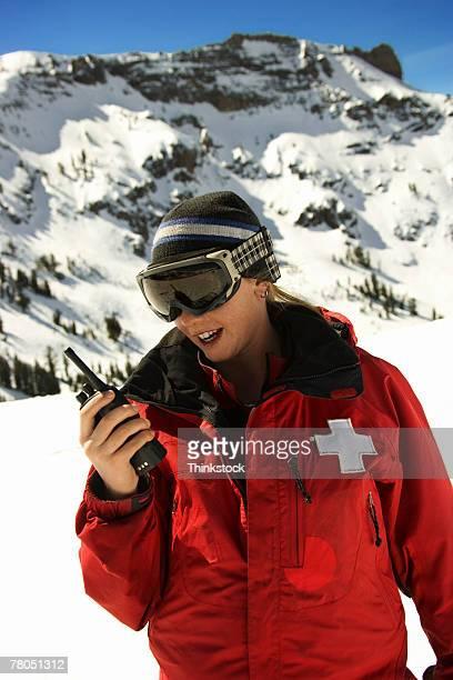 Woman on ski patrol talking on radio