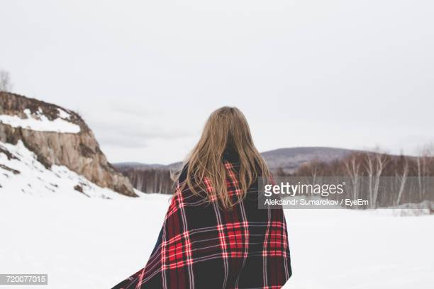 Woman On Snow Covered Landscape Against Sky