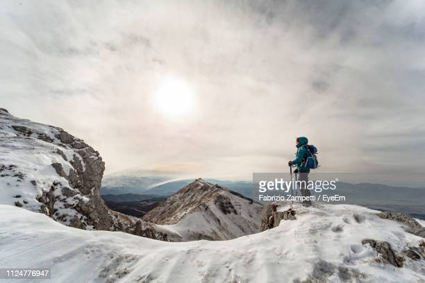 Woman On Snowcapped Mountain Against Cloudy Sky