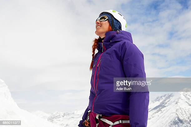 Woman on snow-covered mountain looking up smiling, Saas Fee, Switzerland