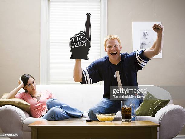 Woman on sofa and man in football jersey standing and cheering