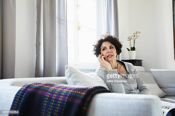woman on sofa and talking on cell phone - curly stock pictures, royalty-free photos & images