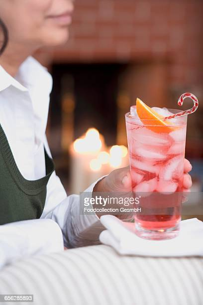 Woman on sofa holding glass of Campari with ice cubes